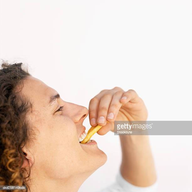 Side view of young man eating French fries
