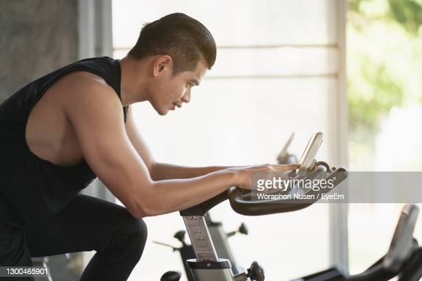side view of young man exercising at gym - peloton stock pictures, royalty-free photos & images