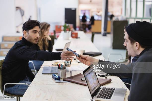 Side view of young man giving smart phone to colleague at desk in office