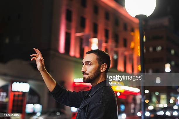 Side view of young man hailing taxi on city street at night