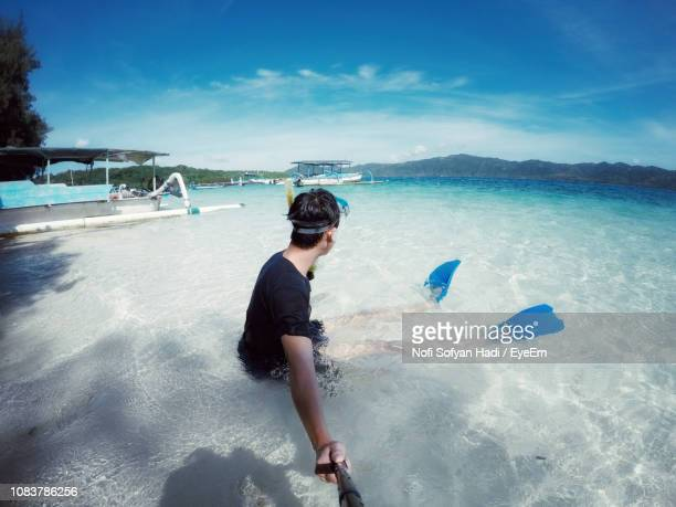 Side View Of Young Man Holding Monopod At Beach Against Sky