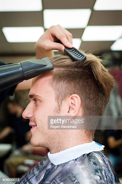 Side view of young man in barbershop having hair blow dried