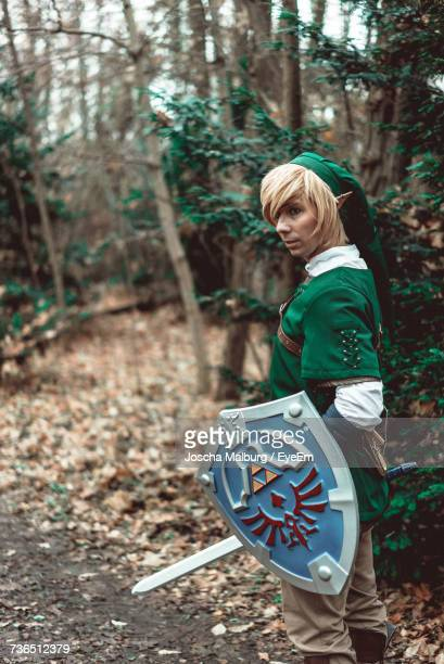 side view of young man in elf costume with sword and shield standing at forest - cosplay stock pictures, royalty-free photos & images
