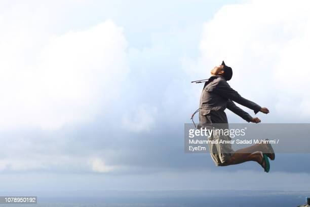 Side View Of Young Man Jumping Against Cloudy Sky