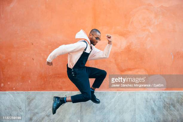 side view of young man jumping against wall - mid air stock pictures, royalty-free photos & images