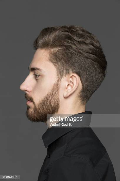 Side view of young man looking away against gray background