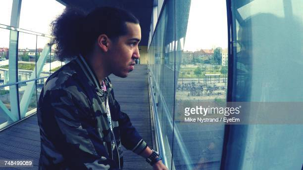 Side View Of Young Man Looking Away While Standing On Footbridge In City