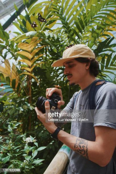 side view of young man photographing plants - クランダ ストックフォトと画像