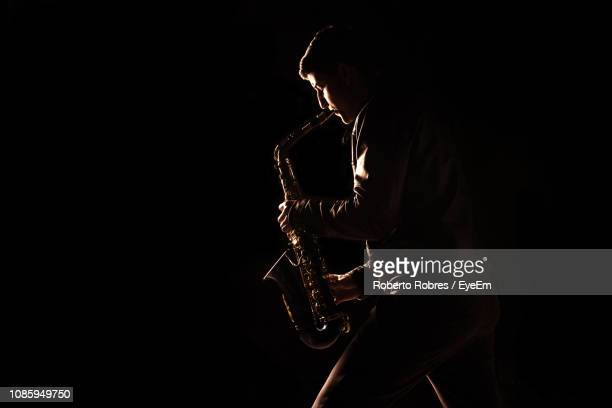 side view of young man playing saxophone against black background - ジャズ ストックフォトと画像