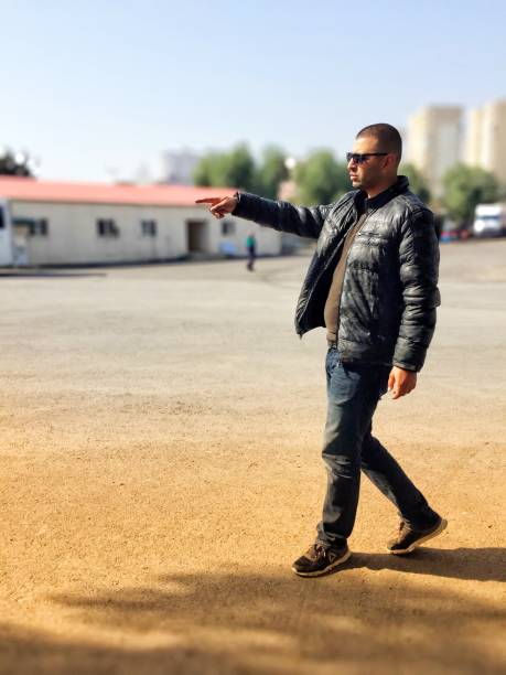 Side View Of Young Man Pointing While Walking On Road Against Sky