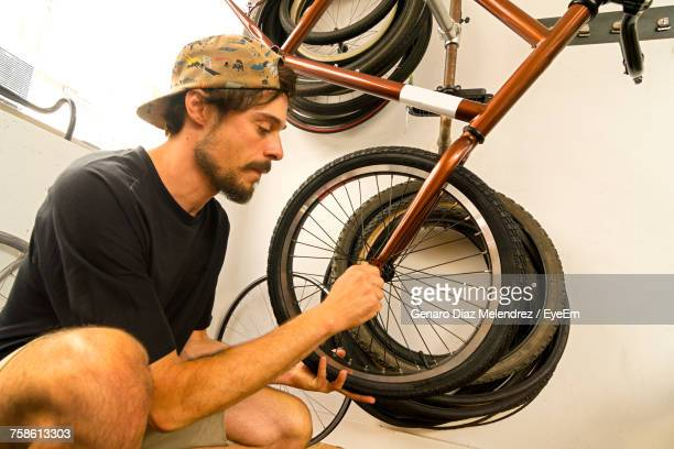 Side View Of Young Man Repairing Bicycle Tire In Workshop