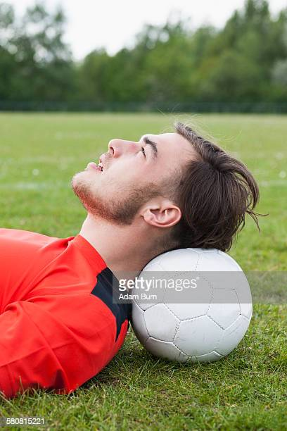 Side view of young man resting head on soccer ball in field