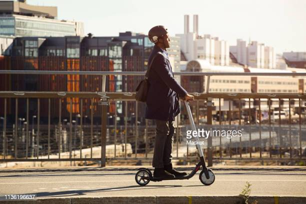 side view of young man riding electric push scooter on bridge in city - electric scooter stock pictures, royalty-free photos & images