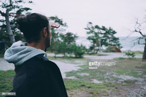 Side view of young man shielding eyes on field at beach