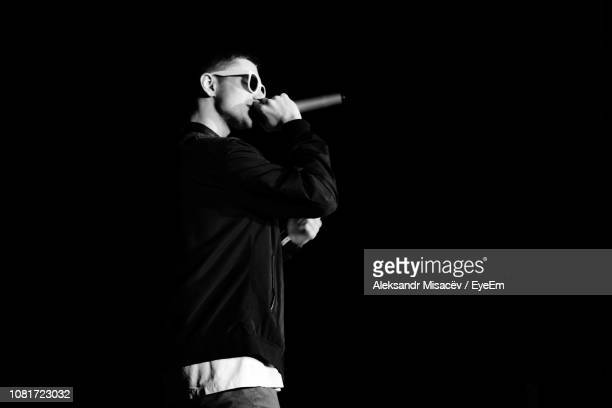 side view of young man singing against black background - rap stock pictures, royalty-free photos & images