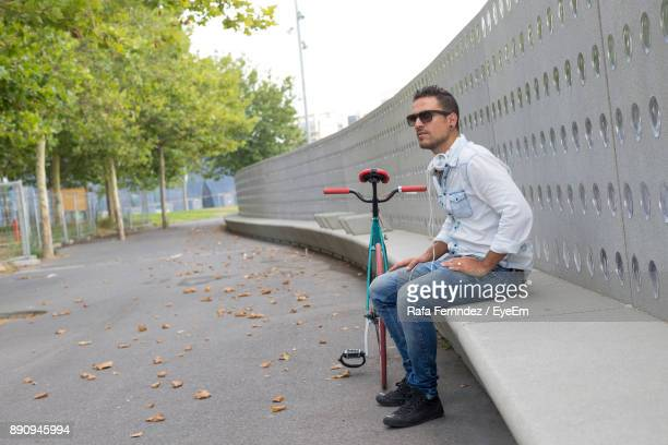Side View Of Young Man Sitting By Bicycle At Park