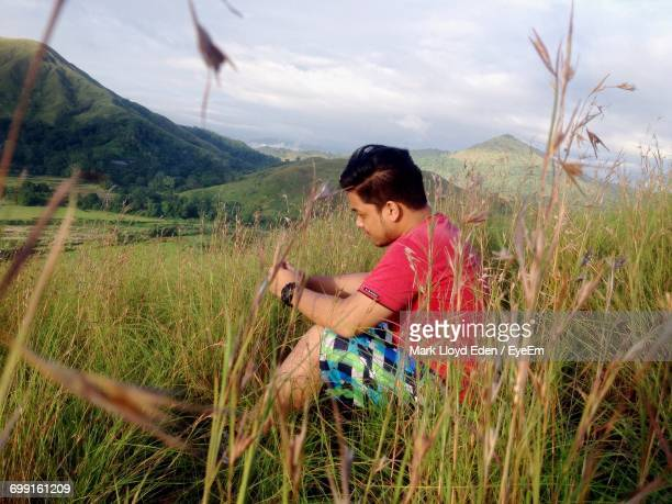 Side View Of Young Man Sitting On Grassy Field Against Mountains