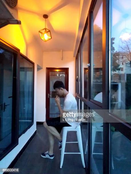 Side View Of Young Man Sitting On Seat By Window At Home
