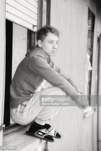 Side View Of Young Man Sitting On Window