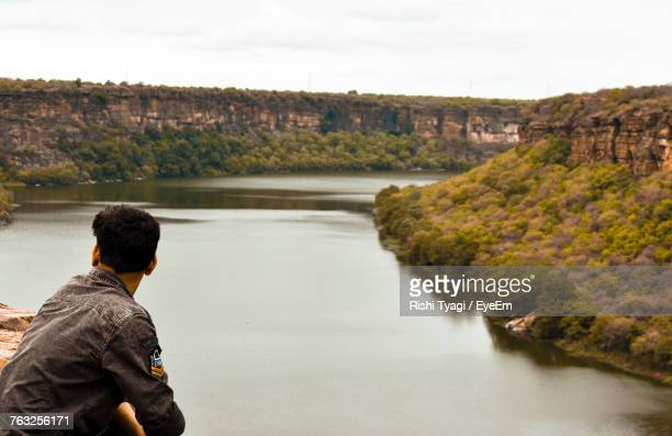 Side View Of Young Man Standing By River Against Sky