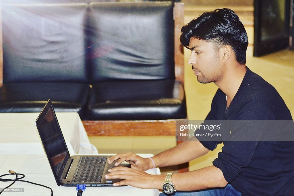 Side View Of Young Man Using Laptop At Table