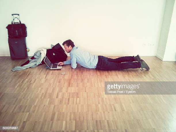Side view of young man using laptop on parquet floor