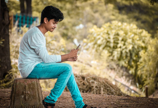 Side View Of Young Man Using Mobile Phone Outdoors
