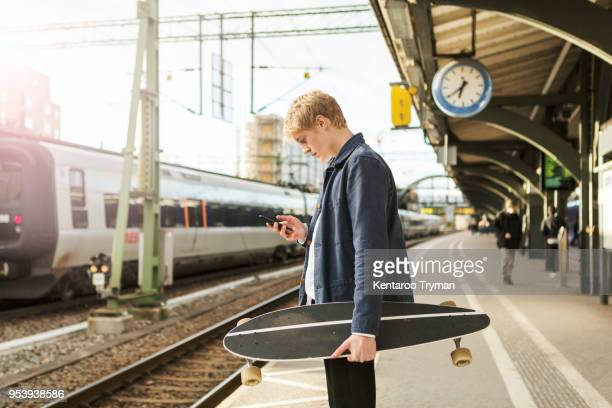 Side view of young man using mobile phone while holding skateboard on railroad station platform