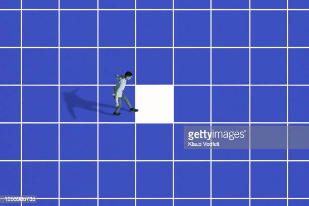 side view of young man walking on blue grid - standing out from the crowd stock pictures, royalty-free photos & images