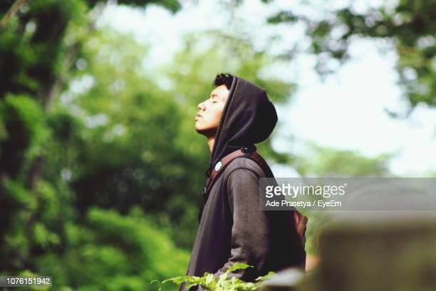 Side View Of Young Man Wearing Hooded Shirt While Standing Amidst Plants