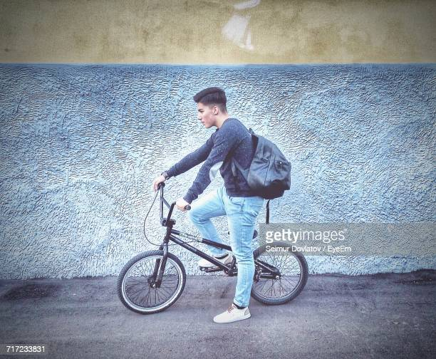 Side View Of Young Man With Backpack And Bicycle On Street Against Wall