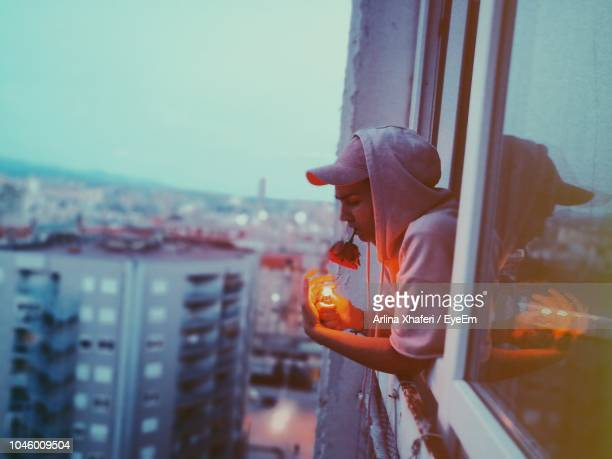 side view of young man with illuminated cigarette lighter carrying rose in mouth while leaning on window - 25 29歳 ストックフォトと画像