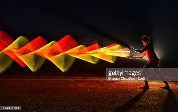side view of young man with illuminated light painting standing against sky at night - fluorescent stock pictures, royalty-free photos & images