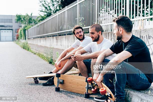 Side view of young men sitting on kerb with skateboards