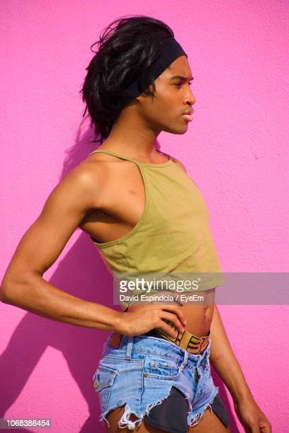 side view of young model with hand on hip standing against pink wall - drag queen fotografías e imágenes de stock