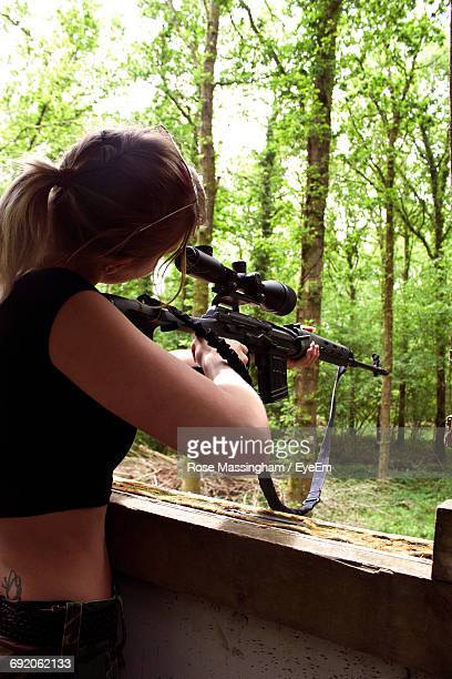 side view of young woman aiming with airsoft gun - air soft gun foto e immagini stock