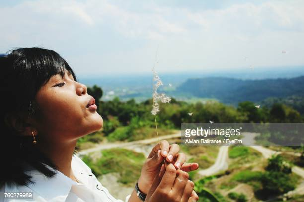 Side View Of Young Woman Blowing Dandelions Against Landscape