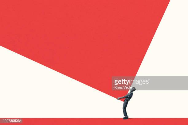 side view of young woman carrying large red block - large stock pictures, royalty-free photos & images
