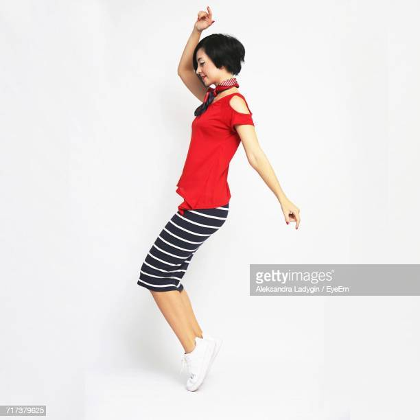 Side View Of Young Woman Dancing Against White Background