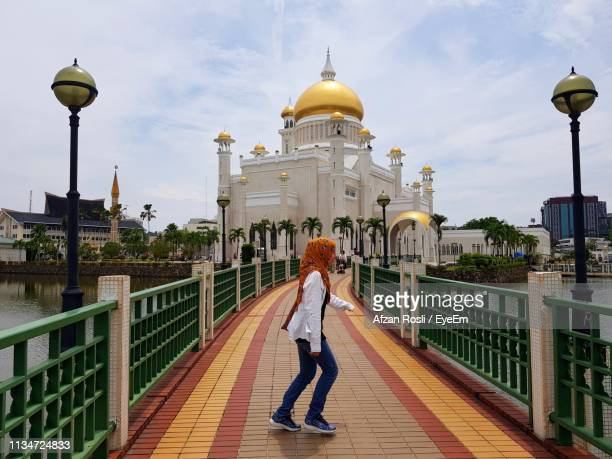 side view of young woman dancing on footpath leading towards mosque - brunei stock pictures, royalty-free photos & images