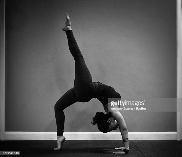 Side View Of Young Woman Doing Yoga In Studio