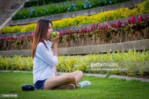 Side View Of Young Woman Eating Granny Smith Apple While Sitting On Field At Park