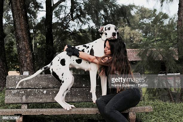 Side View Of Young Woman Embracing Dog On Bench
