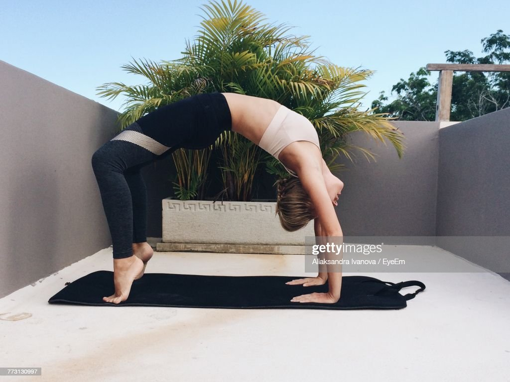 Side View Of Young Woman Exercising Against Clear Sky : Photo