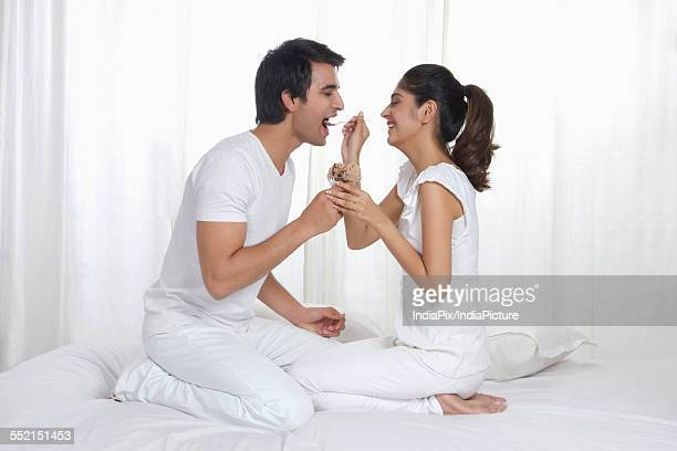Side view of young woman feeding man chocolate ice cream in bed