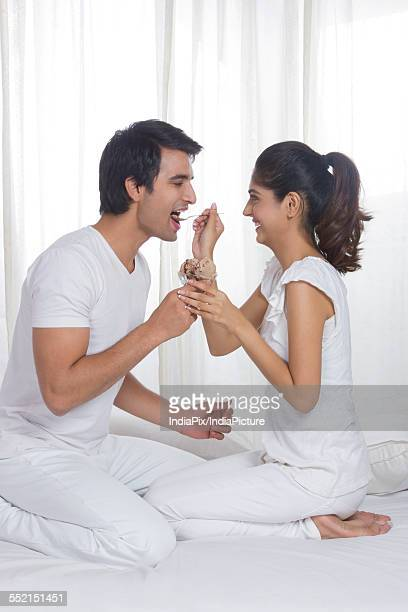 Side view of young woman feeding man ice cream in bed