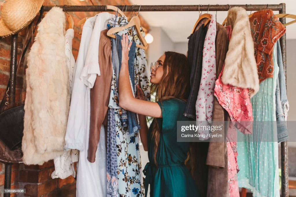 Side View Of Young Woman Hanging Clothes On Rack At Home : Stockfoto