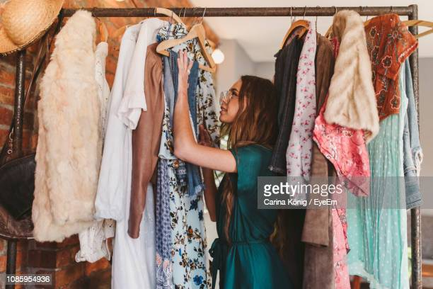 side view of young woman hanging clothes on rack at home - kleid stock-fotos und bilder