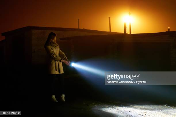 side view of young woman holding flashlight while standing on road against orange sky during sunset - flashlight stock pictures, royalty-free photos & images