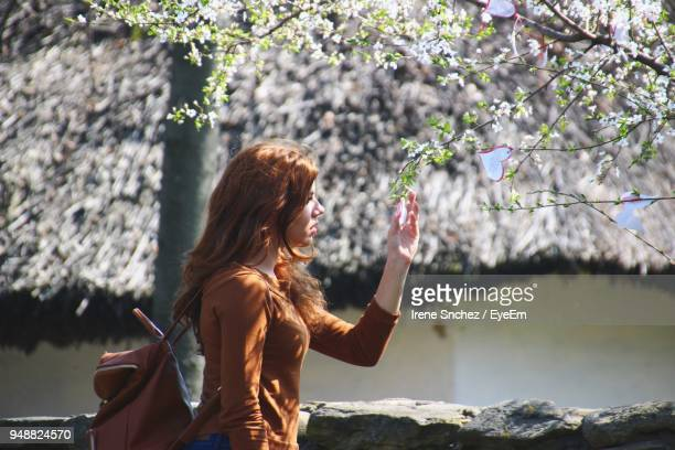 Side View Of Young Woman Holding Heart Shape Labels On Tree